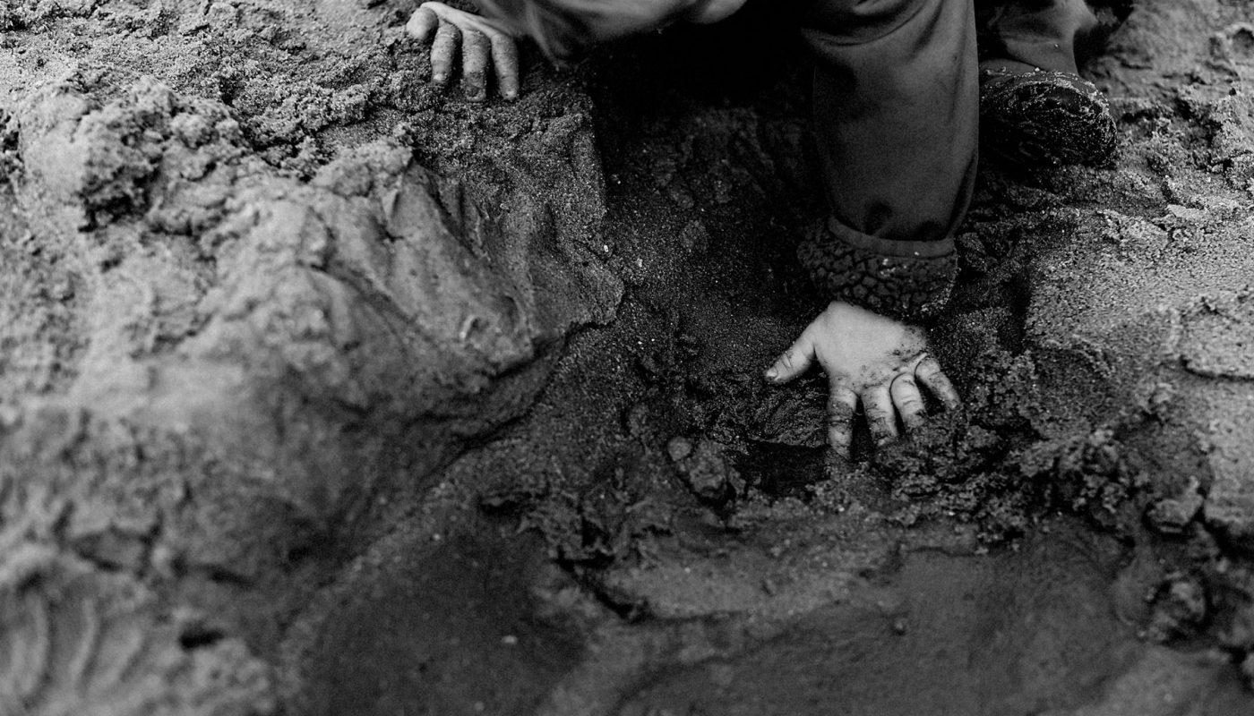 Kinderhand im nassen Sand