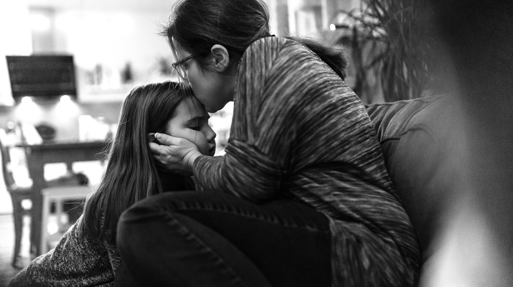 Mama küsst Mädchen auf Stirn